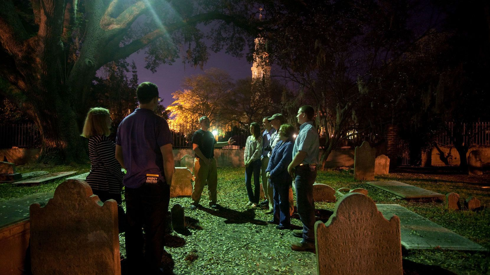 Tour group surrounded by tombstones at a graveyard in Charleston at night