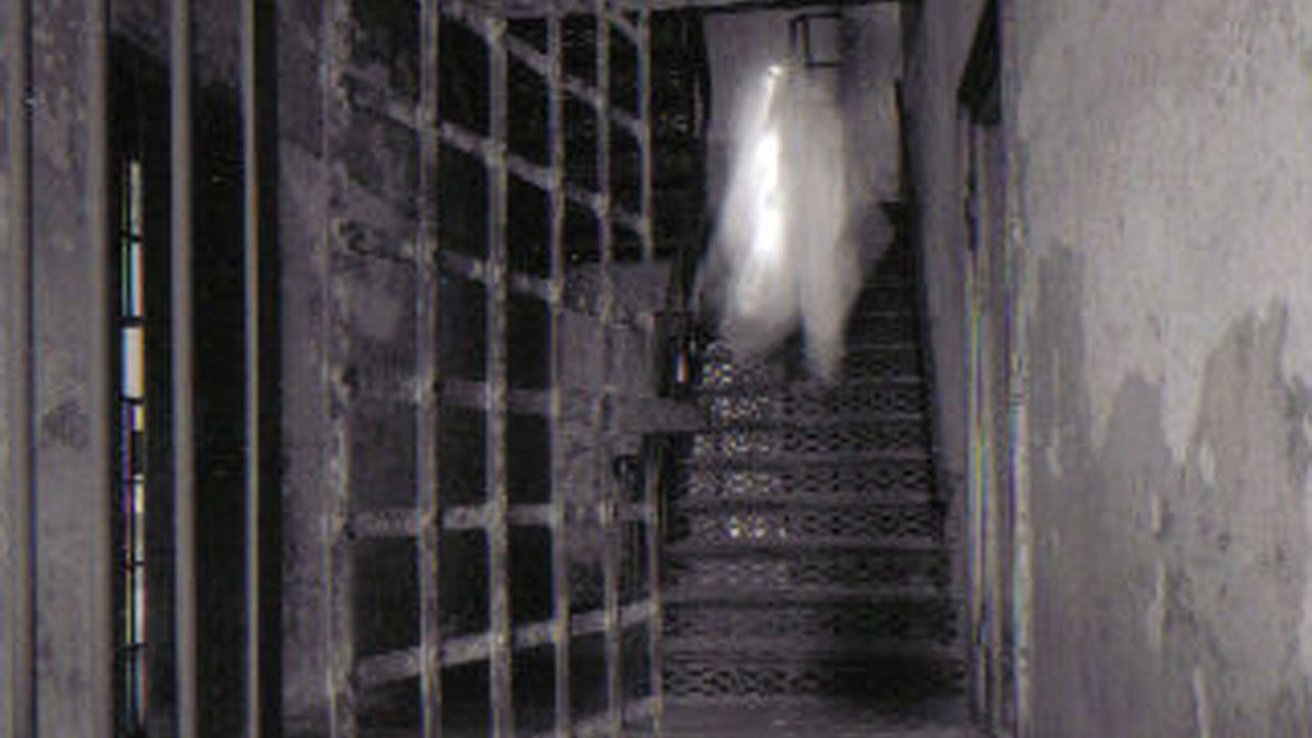 ghostly figure walking down a stairway at the The Haunted Old City Jail in Charleston