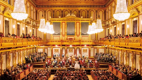 Costumed orchestra and audience in a brightly lit and ornate music hall in Vienna