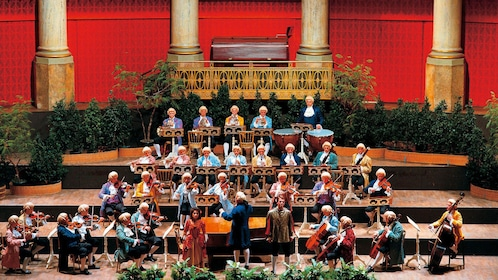 Conductor and orchestra in costumes and wigs during a performance in Vienna