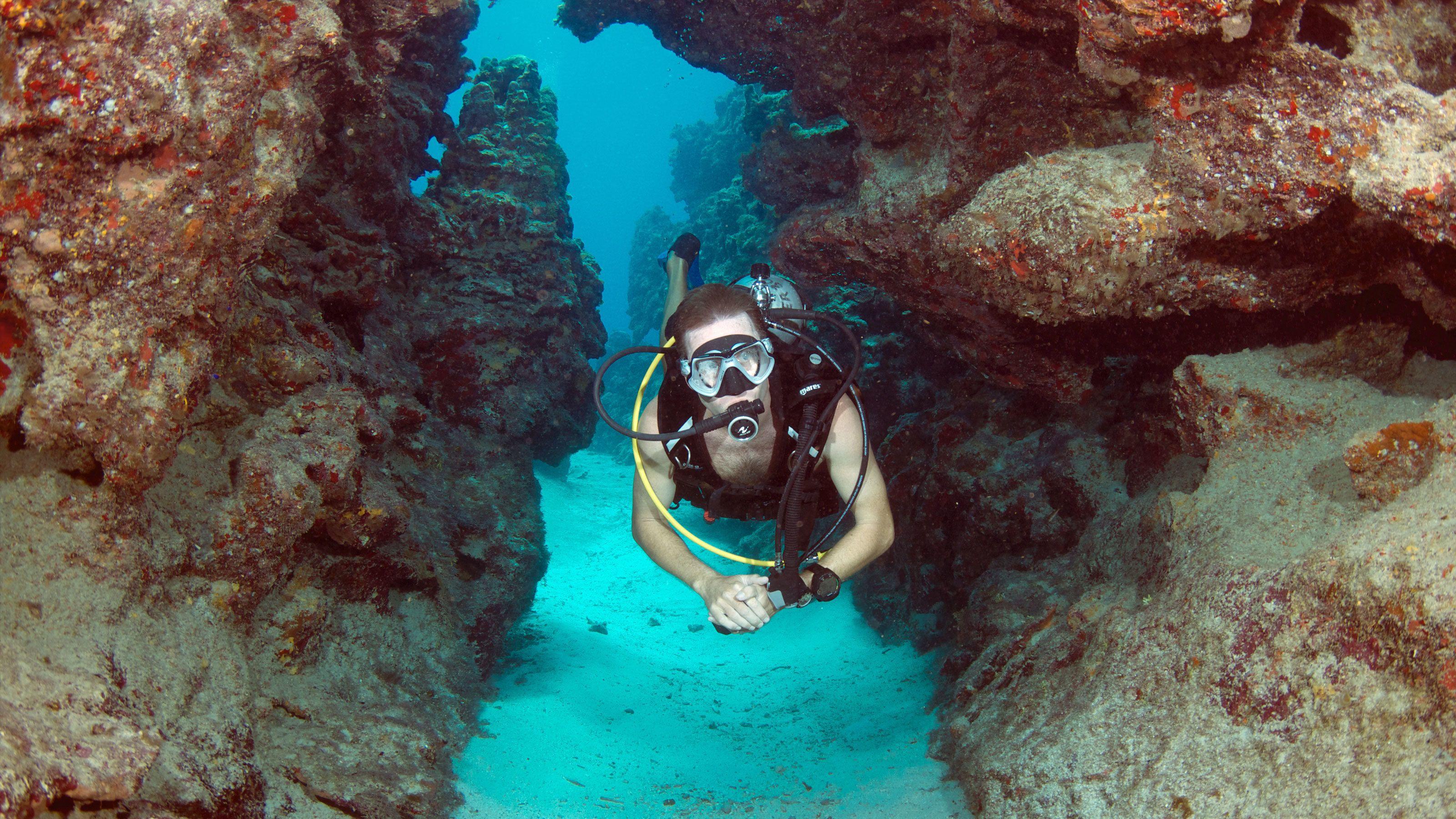 Scuba diver swimming through narrow rock walls in Grand Cayman