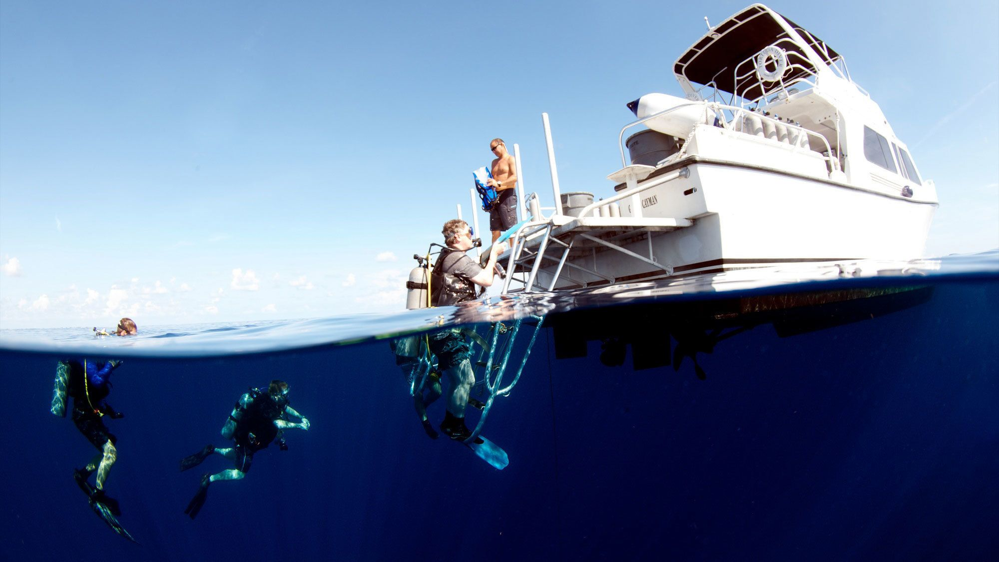 Scuba divers climbing onto a boat in Grand Cayman