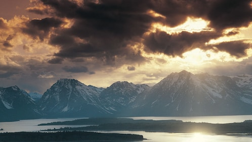View of the mountains at Grand Teton National Park Tour with the sun peaking through the clouds