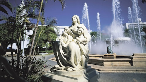Outdoor sculpture of a woman and her children next to a fountain