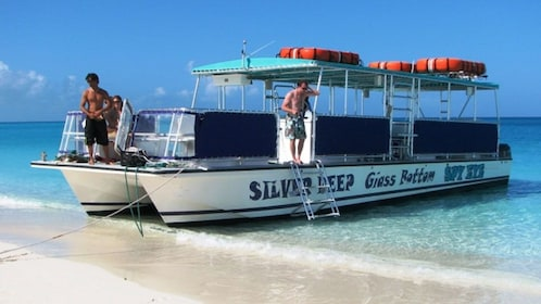 Glass bottom catamaran docked on the beach as operators prepare to set sail