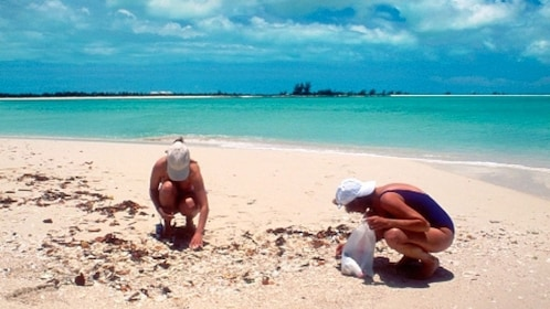 Tourists cleaning up the beach of liter for others to enjoy on the Turks and Caicos Islands