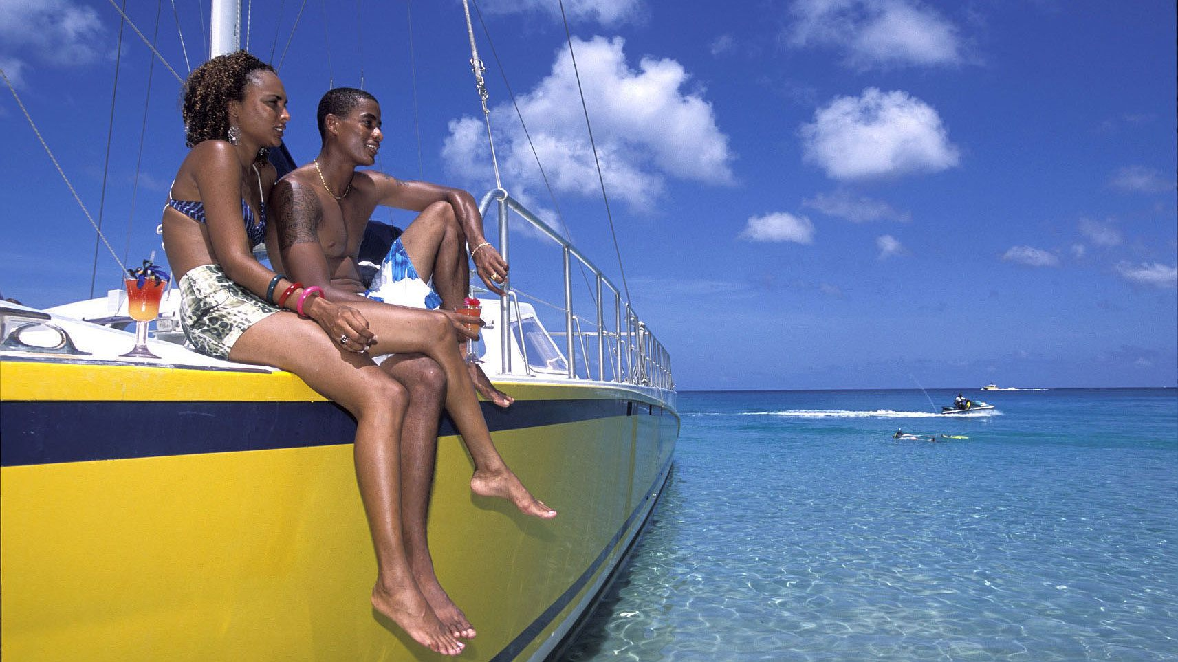 Young friends enjoying view from cruise boat in barbados