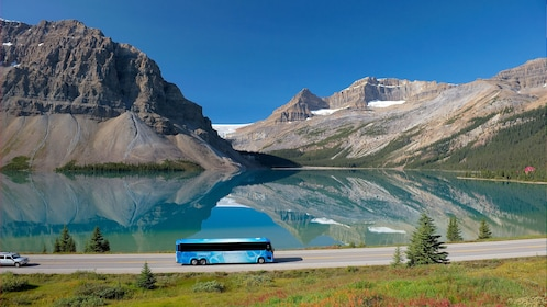 Tour bus driving past a crystal clear lake in Banff