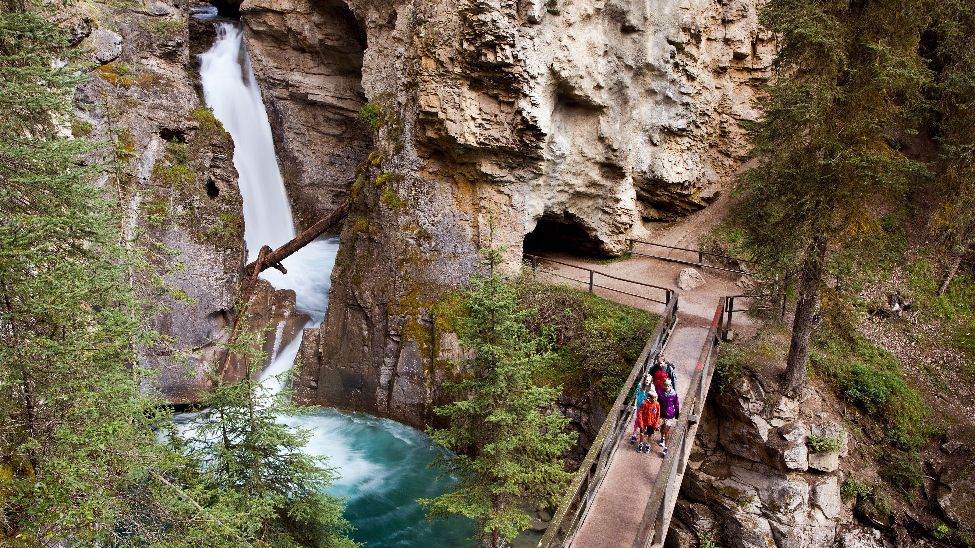 Group walking past a scenic waterfall in Banff