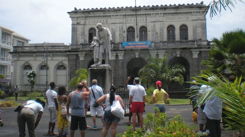 Tourists gathered under statue near a historic building in St Lucia