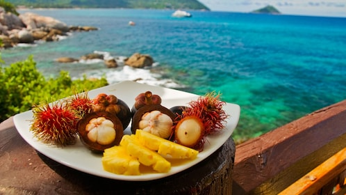 Plate of tropical fruit with rocky coast in the background in St Lucia