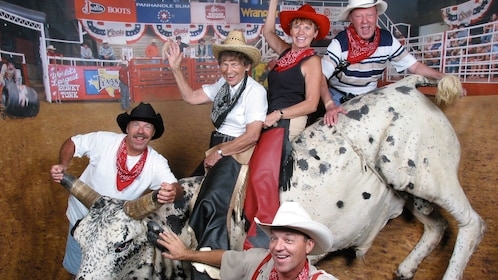 Rodeo enthusiasts pose with prop bull at the Billy Bob's Texas in Dallas
