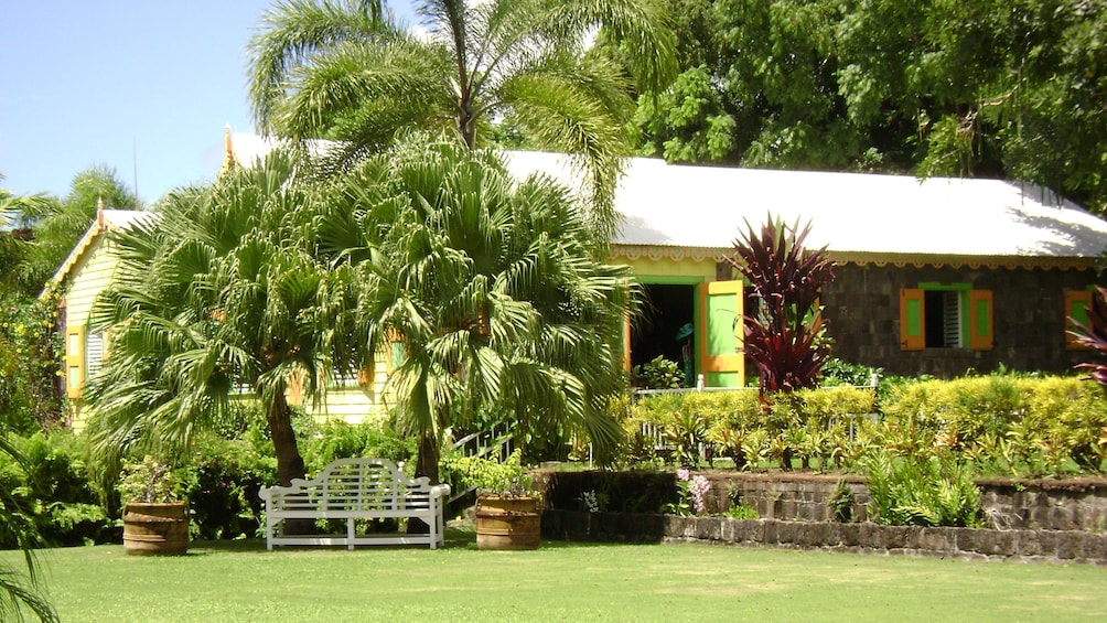 Show item 3 of 10. Colorful and historical Romney Manor and surrounding greenery in St Kitts