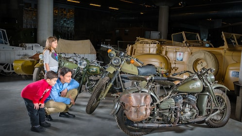 Man with children looking at vintage military motorcycles at the Canadian War Museum in Ottawa