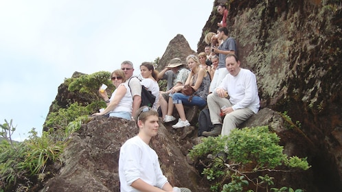 Hiking group sitting on rocks on top of Mount Liamuiga in St Kitts
