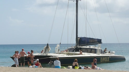 Sunbathers relax on the beach next to an anchored catamaran in St Kitts