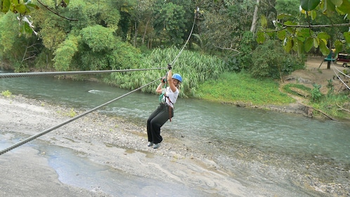 Close view of a person zip lining across some water at the Wacky Rollers Adventure Park