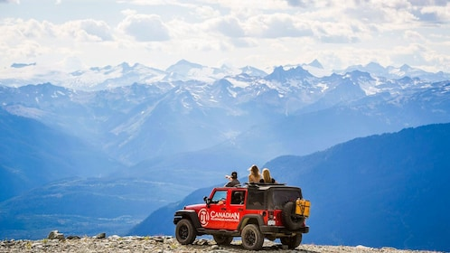 People looking out from top of Jeep at mountain range in Whistler
