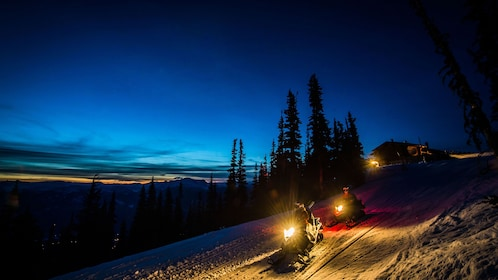 Snowmobile tour on a snowy path down the mountain at night in Whistler