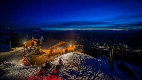 Snowmobiling pair outside a mountain-top cabin overlooking the city below in Whistler