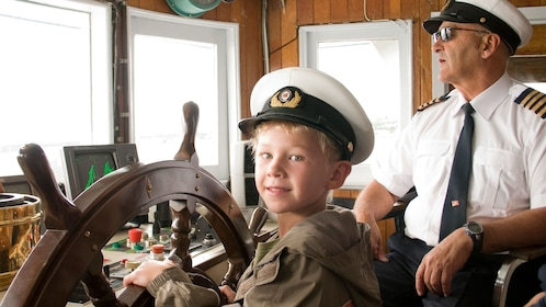 Boy on ship's bridge with captain on the Louis Jolliet river boat in Quebec City