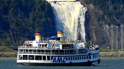 River boat travels towards waterfall in Quebec City