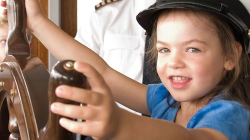 Young girl pretending to steer the Louis Jolliet river boat along the Saint Lawrence River