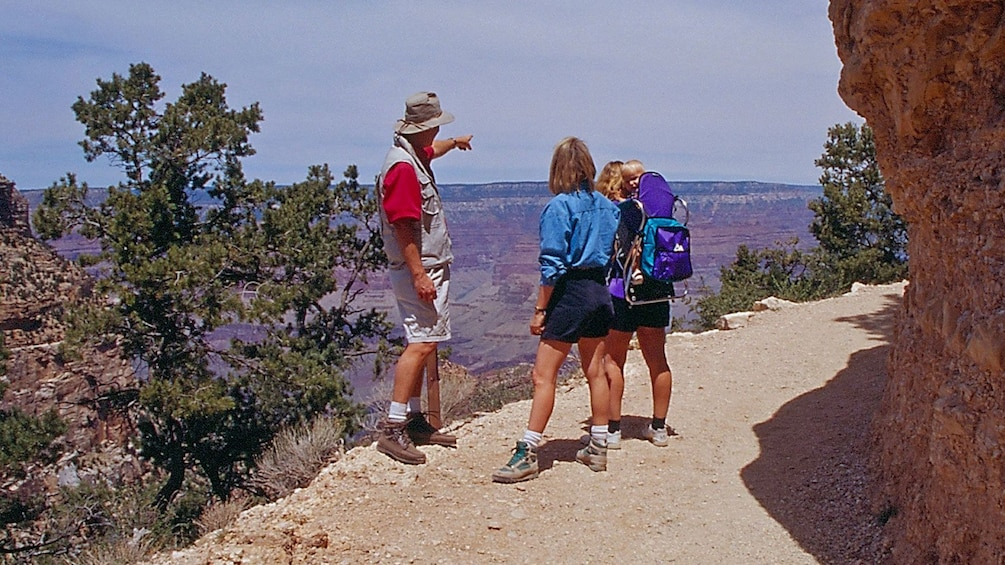 Show item 3 of 5. Tour guide directing some tourists at the Grand Canyon