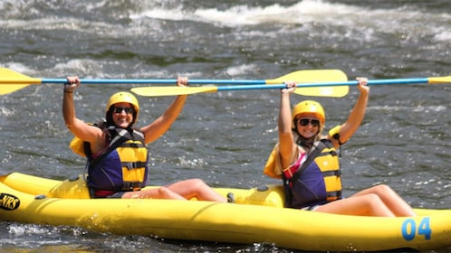 Two people in a raft smiling during a Pigeon River whitewater rafting trip in Tennessee