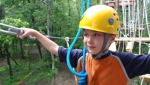 Close view of the child walking across the ropes bridge during a ropes course in the heart of the Smokey Mountains