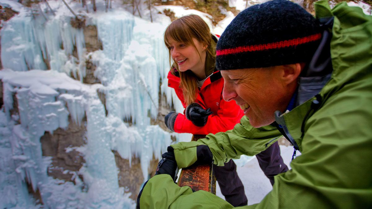 A couple take a closer look at the ice formations of Johnston Canyon