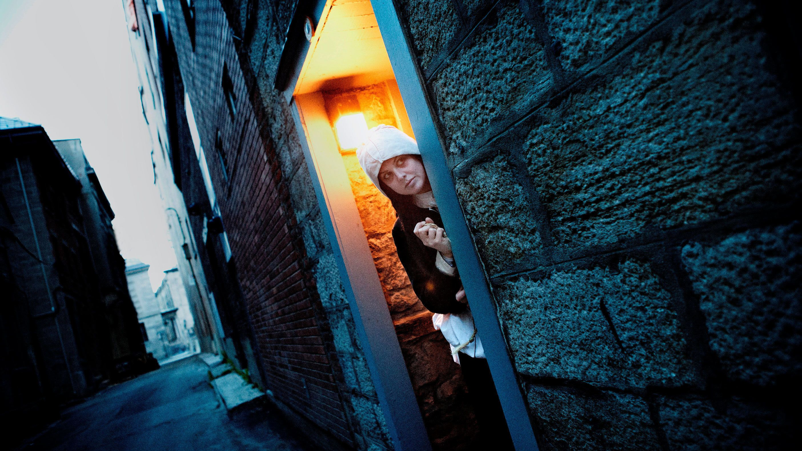 Woman peering out from doorway in Old Montreal Ghosts & Spirits Walking Tour