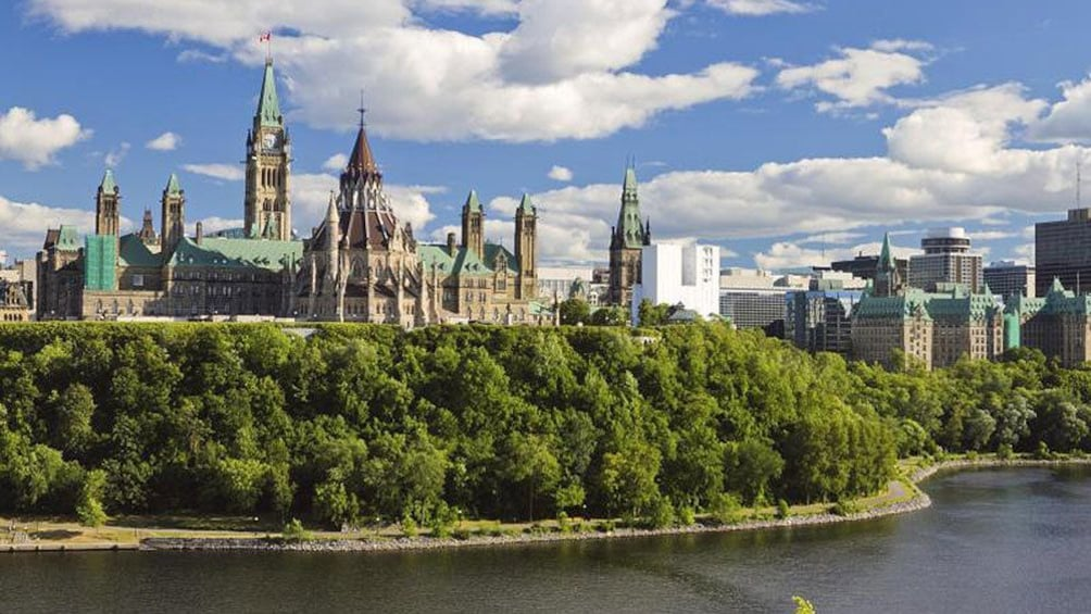 Green towers of Parliament Hill near the river in Ottawa
