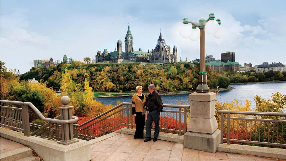 Couple standing a view point with the river and Parliament Hill in the background in Ottawa