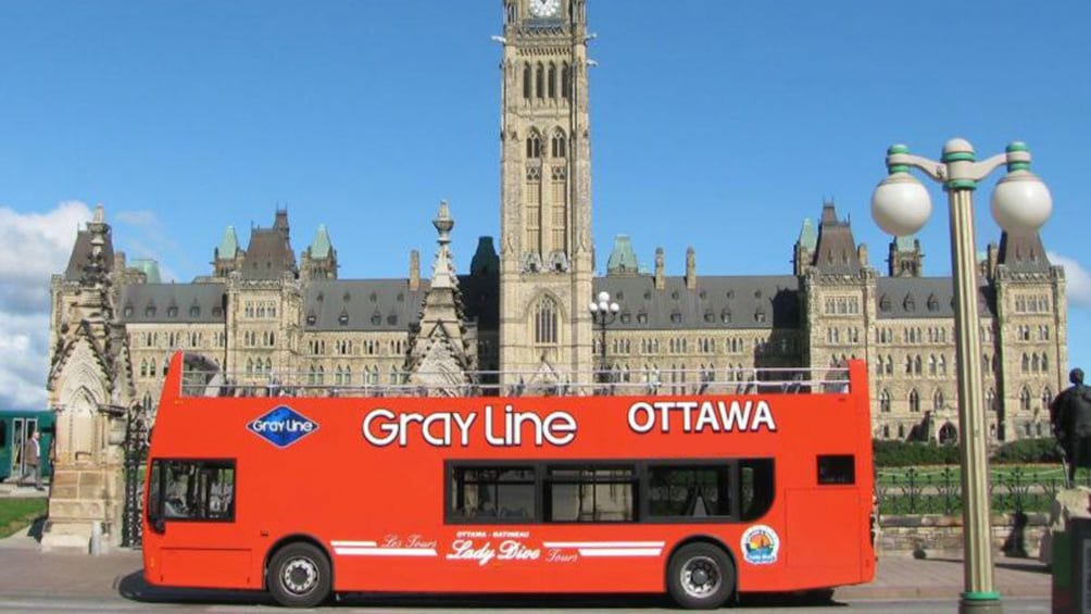 Hop-On Hop-Off bus parked in front of the Centre Block building on Parliament Hill in Ottawa