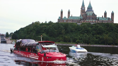 Amphibious vehicle in the Ottawa River with the green towers of Parliament Hill in the background