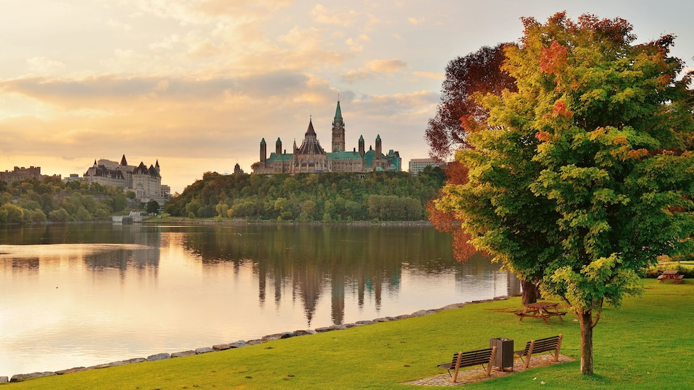 Show item 4 of 4. The Ottawa River and Parliament Hill in autumn at dusk in Ottawa