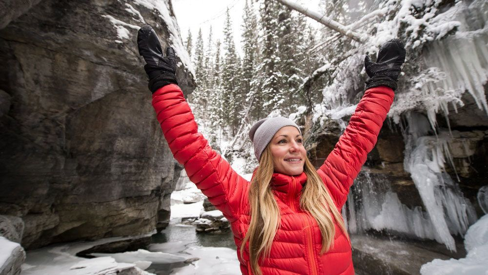 Woman has her hands raised as she enjoys her time on the Maligne Canyon Icewalk in Jasper