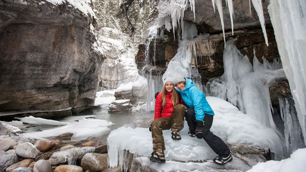 Two friends smiling on a Maligne Canyon Icewalk in Jasper