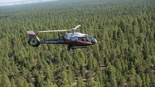 Helicopter flying above green trees in the Grand Canyon area