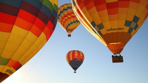 Hot air balloons lift off high into the sky above Arizona