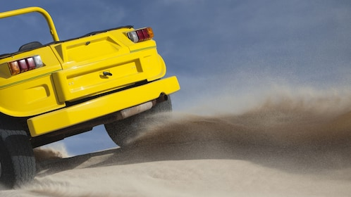 yellow dune buggy kicking up sand in the dunes