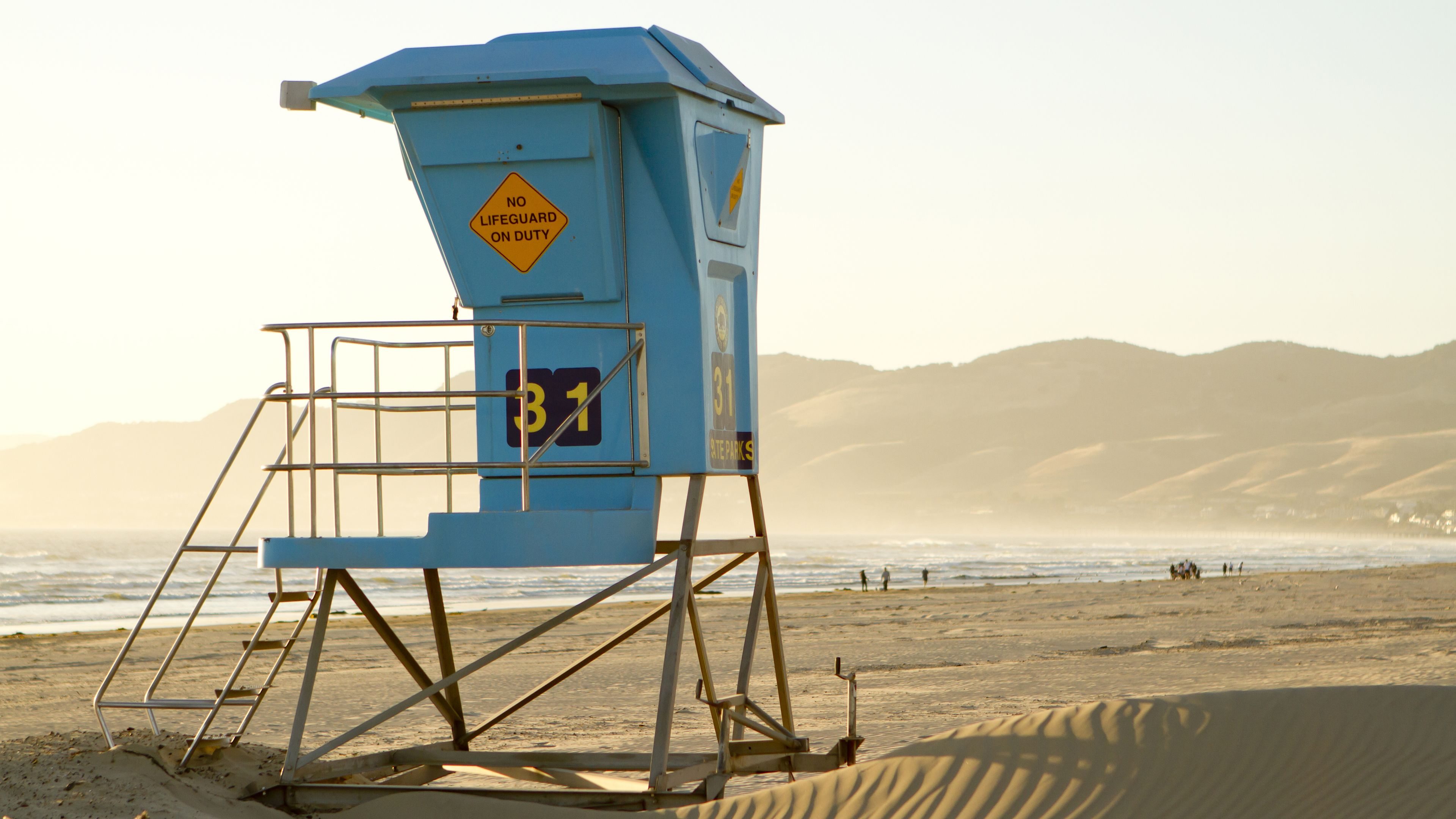 Lifeguard stand on beach at sunrise