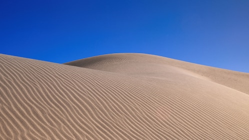 Sand dunes against the clear blue sky