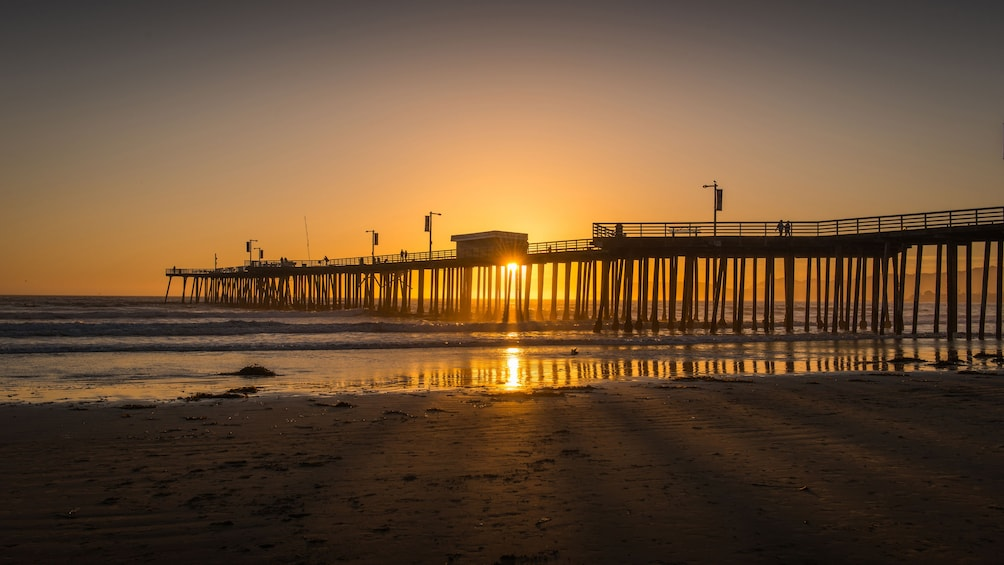 Show item 2 of 5. Pier jutting out into ocean at sunset