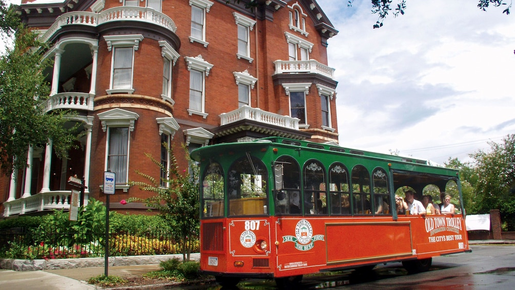 Show item 3 of 10. Hop on, hop off trolley going through downtown Savannah