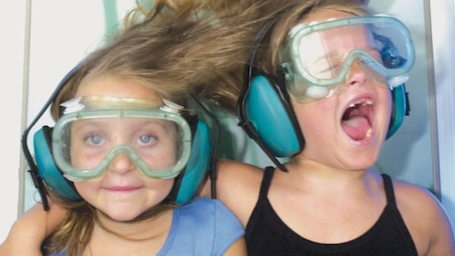 Two girls experiences a the affects of a wind tunnel
