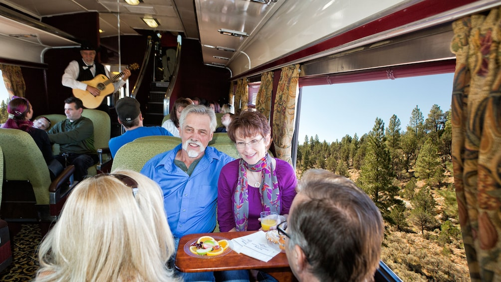 Show item 3 of 7. Couple smiles before enjoying a meal aboard the train in the Grand Canyon Railway