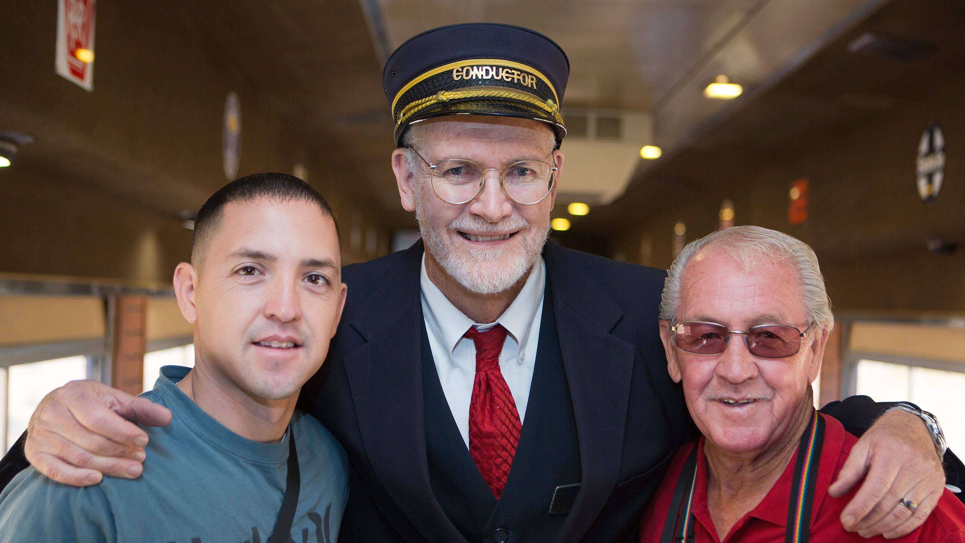 Two men smile with the train conductor aboard the train at the Grand Canyon Railway