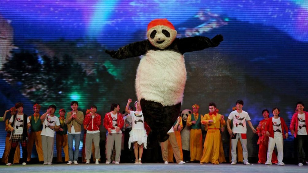 Show item 3 of 10. Performer in panda suit jumping on stage in Beijing